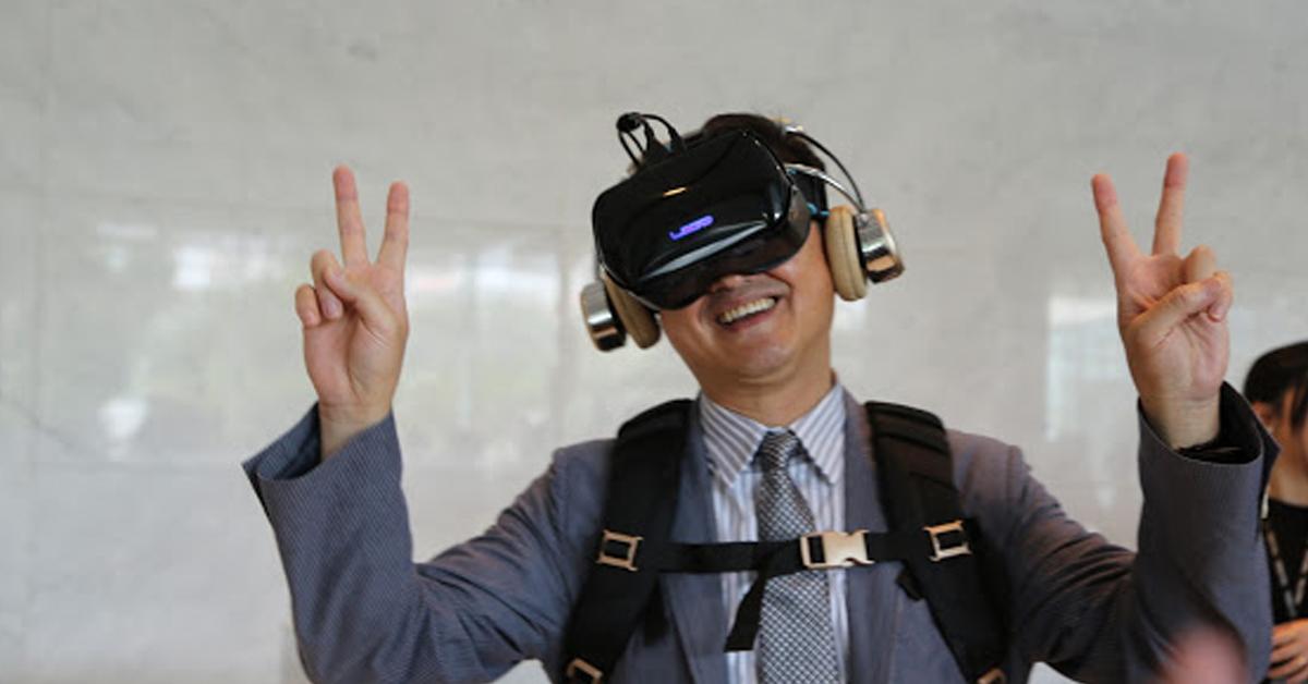 童子賢試戴虛擬實境頭戴式裝置與背包配件。照片來源:James Huang攝影